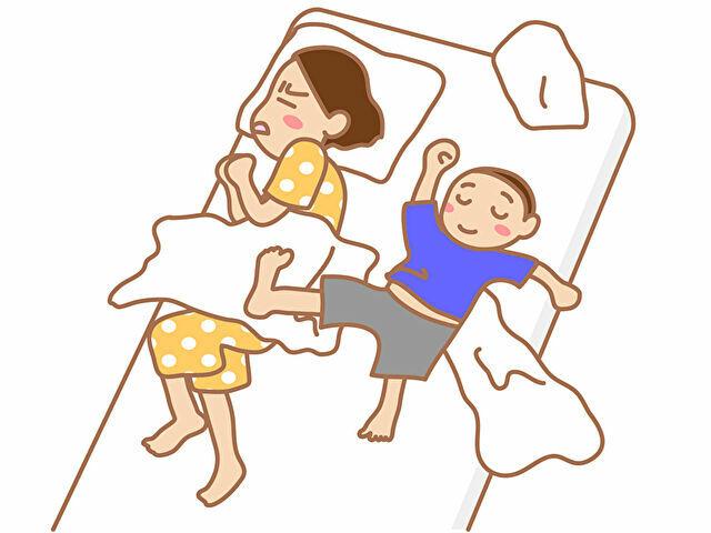 子供の足が体に乗って寝苦しい母親
